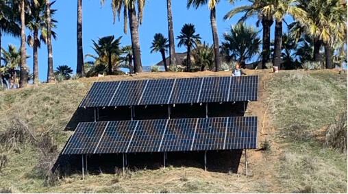An array of solar panels mounted on a hill.