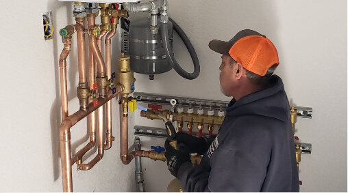 A Technician looking at copper piping