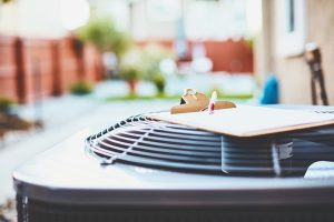 outside-air-conditioner-unit-with-clipboard-resting-on-top