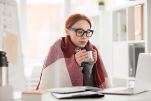 woman-huddled-under-blanket-drinking-out-of-mug