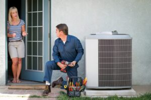 technician-working-on-outdoor-ac-unit-with-homeowner-in-background