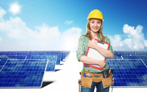 woman-in-hard-hat-with-clipboard-standing-in-front-of-rows-of-solar-panels